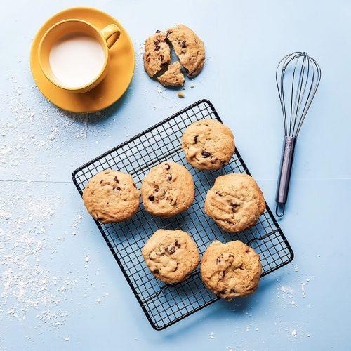 cookies sobre fondo azul y taza de leche